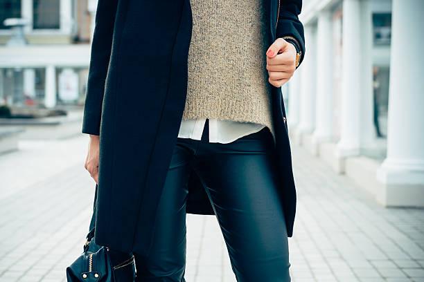 nahaufnahme einer frau im einem pullover, jacke, schwarze hose - leder leggings stock-fotos und bilder