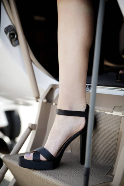 Close-up of a woman in high heels stepping off a private jet stock photo