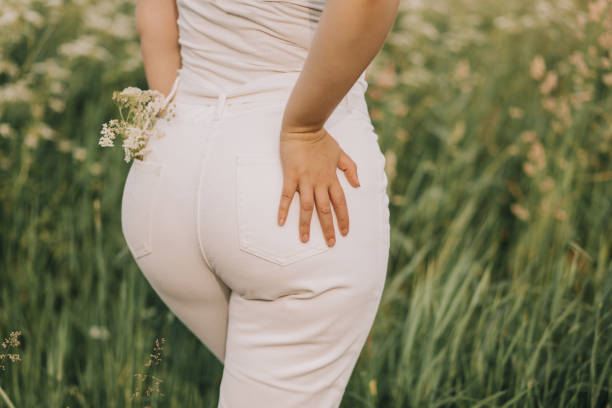 Closeup of a woman in white jeans on a field background. Closeup of a woman in white jeans on a blooming field background. Stylish look, fashion for curvy women, outdoor recreation. hot sexy butts stock pictures, royalty-free photos & images