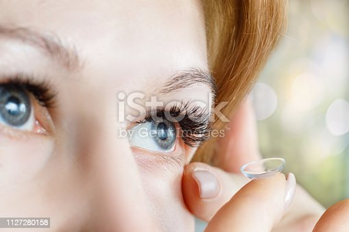 istock A closeup of a woman inserting a contact lens into her eye. 1127280158
