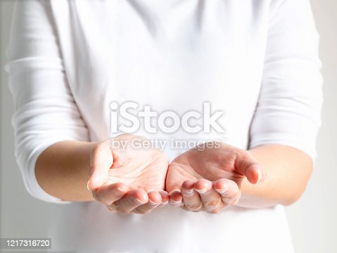 883034410 istock photo Close-up of a woman opening her palms that symbol of giving or donating. 1217316720