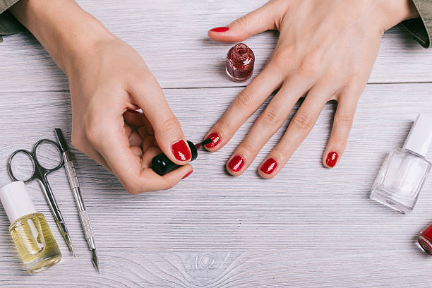 close-up of a woman paints her nails with red lacquer - nägel lackieren stock-fotos und bilder