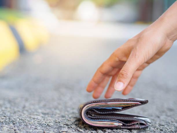 close-up of a woman picking up fallen wallet on road side - leder portemonnaie herren stock-fotos und bilder