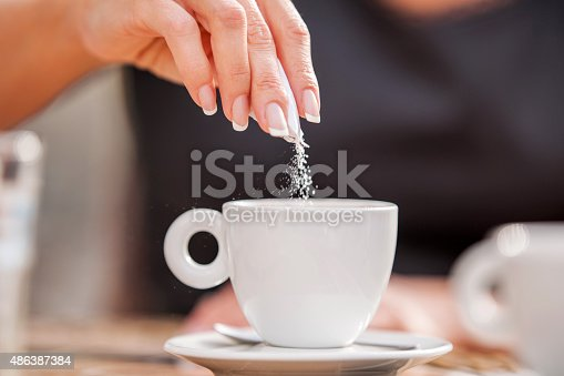 Woman's hand pouring sugar in her coffee.
