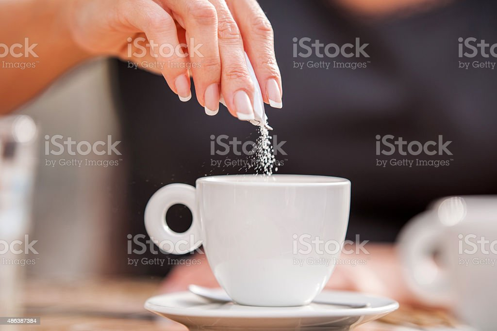 Close-up of a woman pouring sugar in coffee cup. stock photo