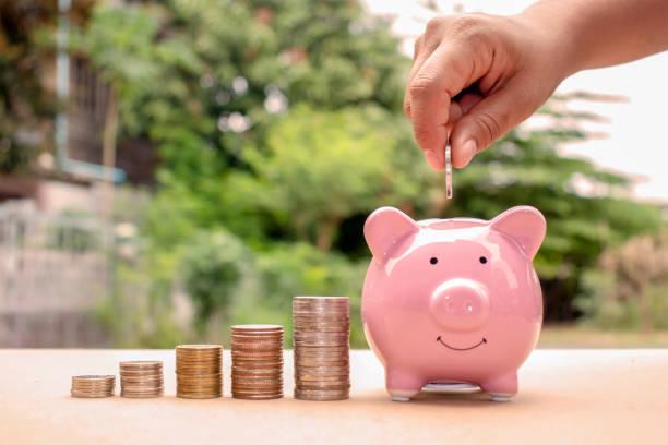 primer plano de una mujer poniendo una moneda en una alcancía, incluyendo una pila de monedas, ahorro de ideas y crecimiento financiero. - gerente de cuentas fotografías e imágenes de stock