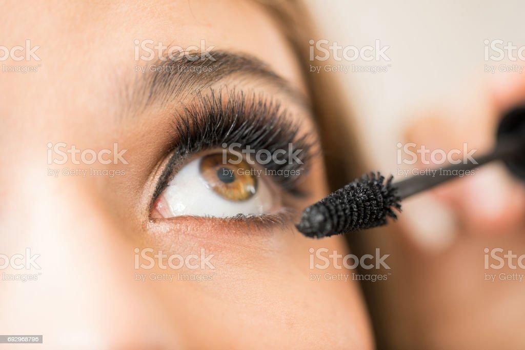 Closeup of a woman putting mascara on stock photo