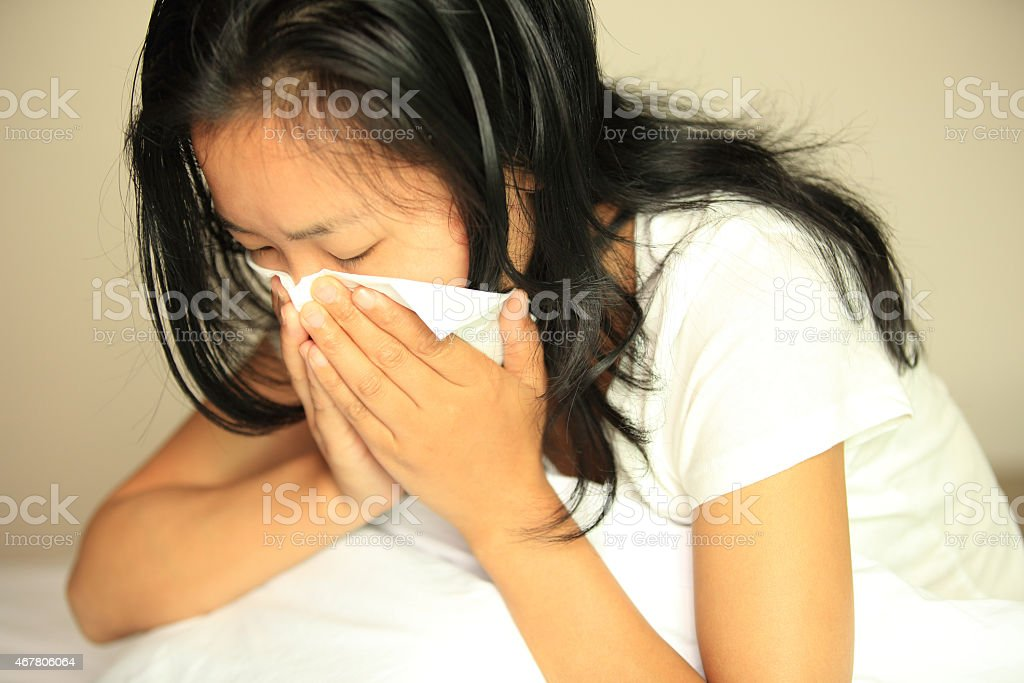 A close-up of a woman sneezing into a tissue stock photo