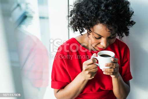 A close-up of a woman standing by the window holding a cup of coffee, smelling it. Copy space.