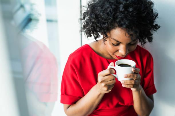 un primer plano de una mujer de pie junto a la ventana con una taza de café. - café bebida fotografías e imágenes de stock