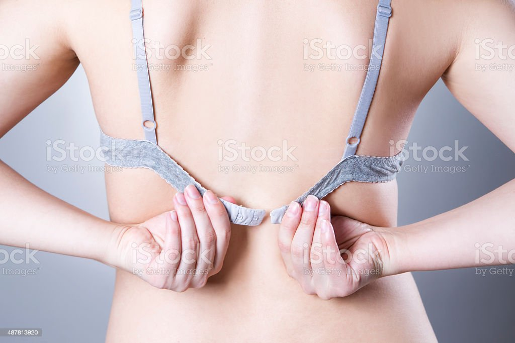 Closeup of a woman undressing and unhooking her bra stock photo