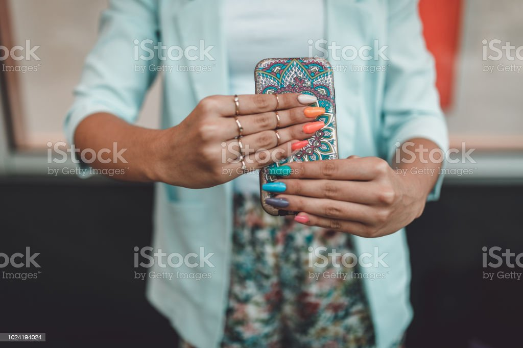 Close-up of a woman using smart phone outdoors in the city stock photo