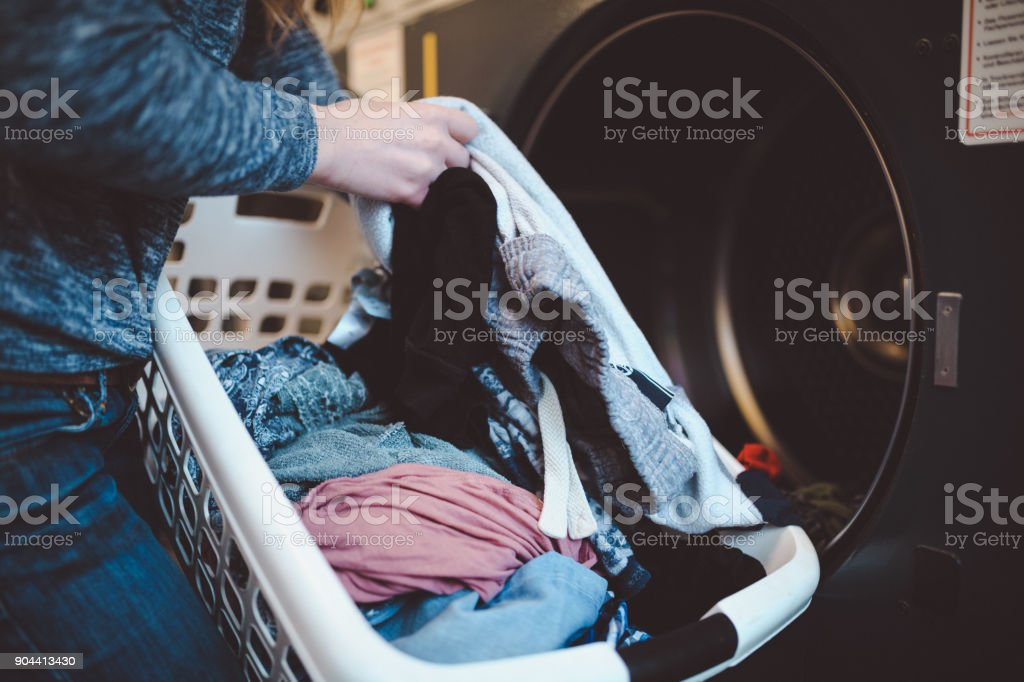 Close-up of a woman with a laundry basket washing clothes stock photo