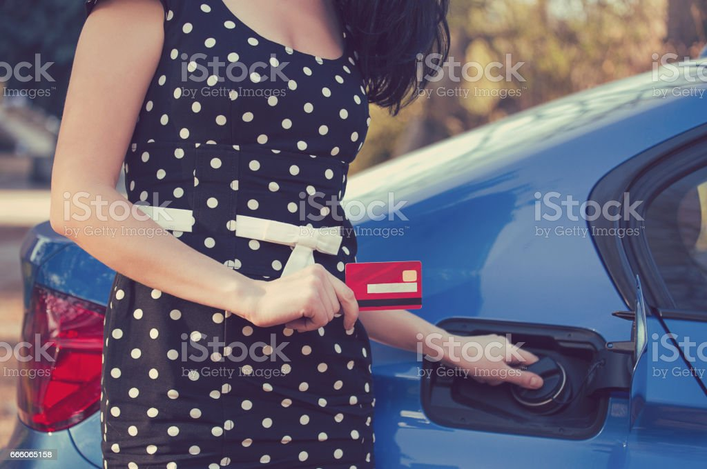 Closeup of a woman with credit card opening fuel tank of her new car royalty-free stock photo
