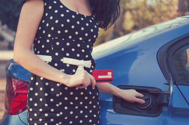 Closeup of a woman with credit card opening fuel tank of her new car stock photo