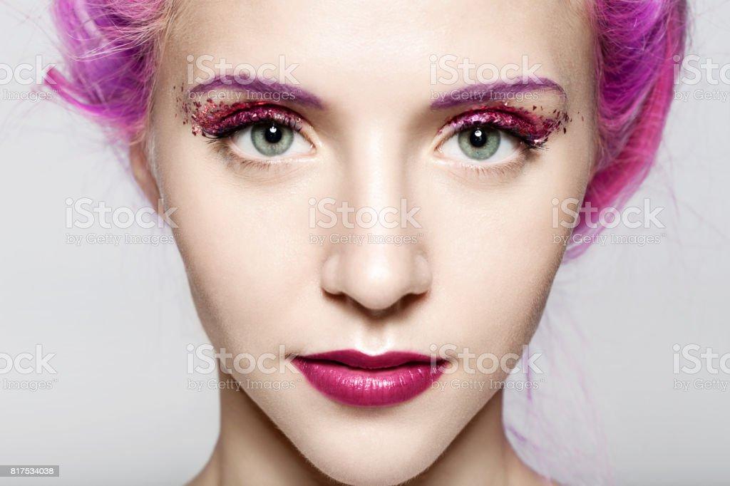 Close do rosto de uma mulher com uma maquiagem moda brilhante em tons violetas com brilhos - foto de acervo