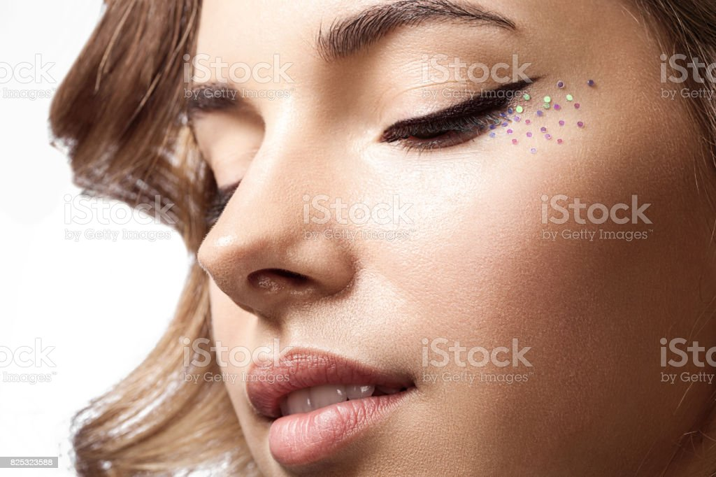 Close-up of a woman's face with a with a natural beauty and shiny  makeup  with sparkles stock photo