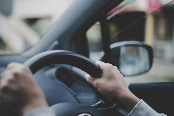 車のハンドルを保持している女性の手のクローズ アップ - 車 ストックフォトと画像