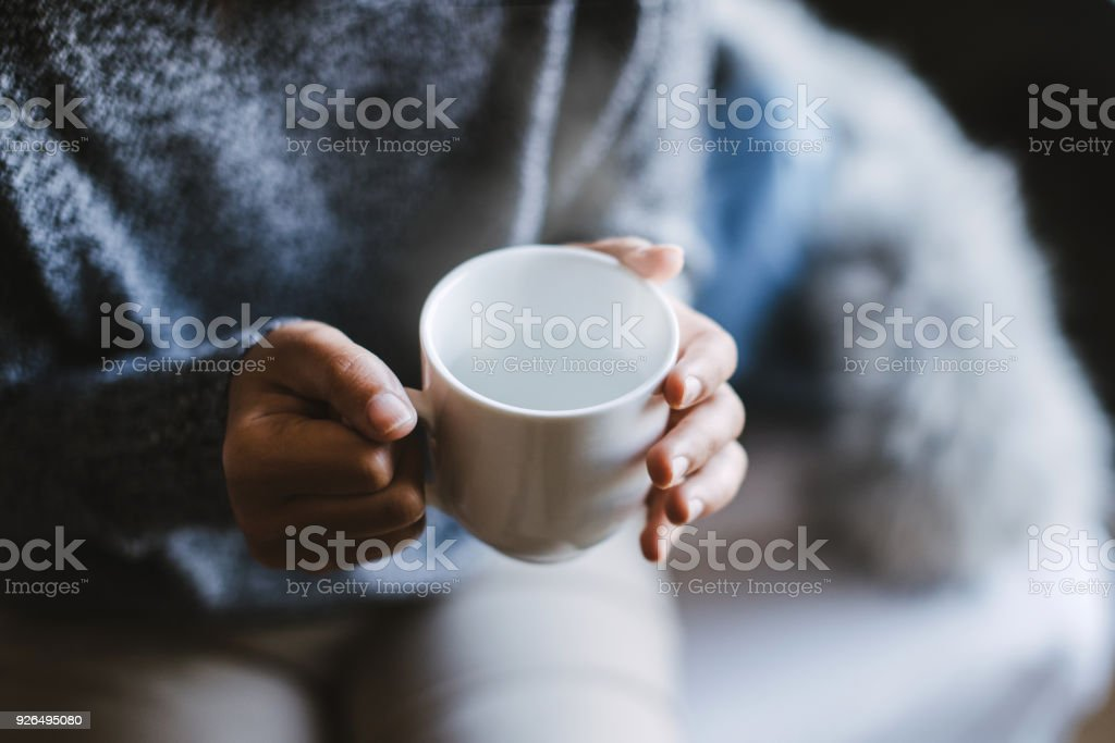 Close-up of a woman's hand holding a cup of hot water, vintage tone. stock photo
