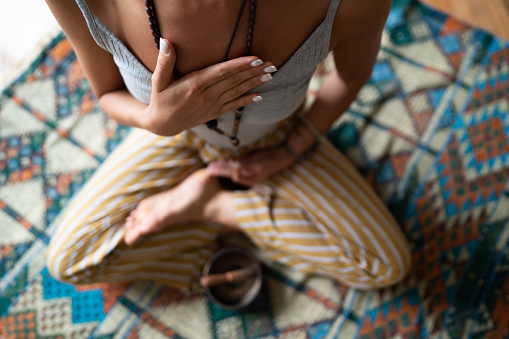 Close-up of a woman's hand on her chest while doing breathing exercises and meditating at home. Caucasian woman sitting in a lotus position, practicing pranayama.