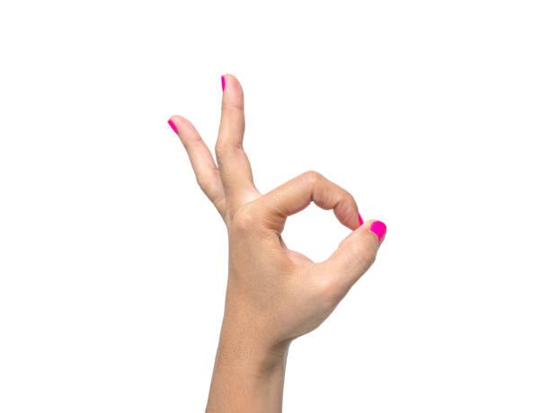 nahaufnahme der hand einer frau zeigt ok zeichen mit einem rosa nagellack isoliert auf einem weißen hintergrund. - bester nagellack stock-fotos und bilder