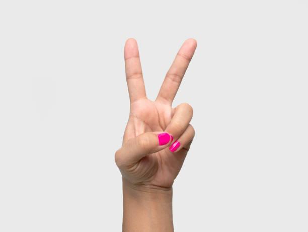nahaufnahme der hand einer frau zeigt v-zeichen mit einem rosa nagellack isoliert auf weißem hintergrund. - bester nagellack stock-fotos und bilder