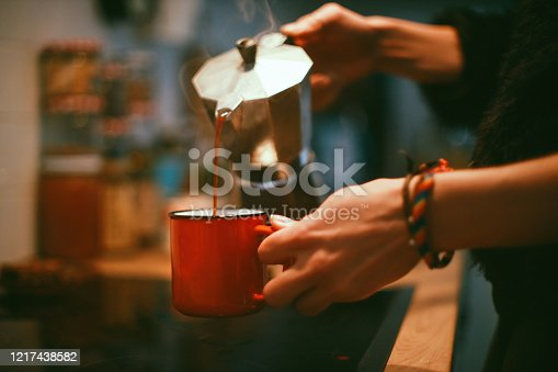 Close-up of a young woman's hands while she's pouring coffee.