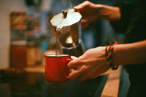 Close-up of a woman's hands pouring coffee