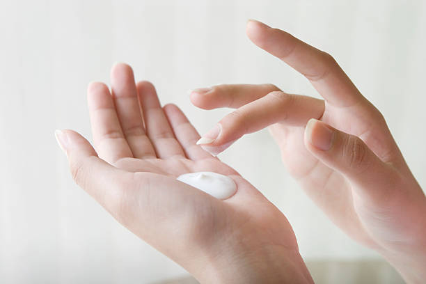 close-up of a woman's hands while applying white lotion - vochtinbrengende crème stockfoto's en -beelden