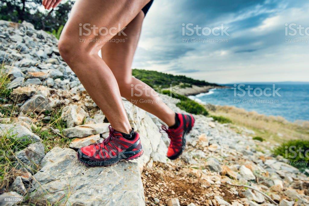 Gros plan sur les jambes de la femme en haut d'une colline rocheuse photo libre de droits