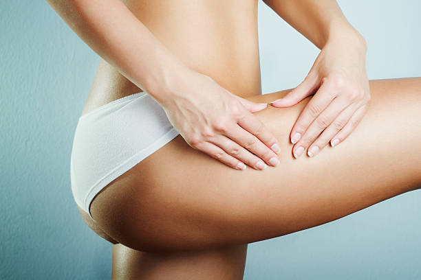 A closeup of a woman's midsection, pinching thigh cellulite  stock photo