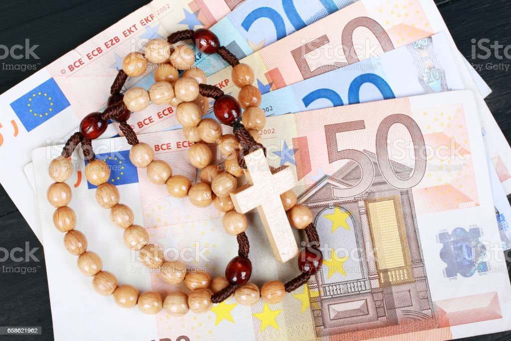 Closeup of a wooden rosary on Eurp banknotes stock photo
