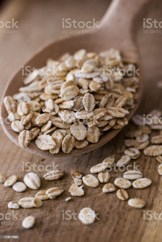 Close-up of a wooden spoon with uncooked rolled oats royalty-free stock photo