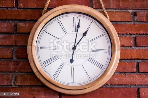 671883446istockphoto Close–up of a wooden wall clock with roman numerals hanging in a red brick wall. 961138720