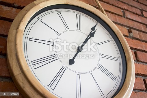 671883446istockphoto Close–up of a wooden wall clock with roman numerals hanging in a red brick wall. 961138948