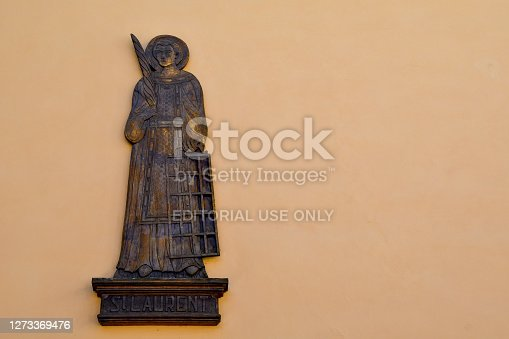 Pré-Saint-Didier, Aosta / Italy - July 06 2020: Detail of a wood artwork representing Saint Lawrence, one of the seven deacons of Rome, where he was martyred in 258 during the persecution decidedmartyr by the Roman emperor Valerian.