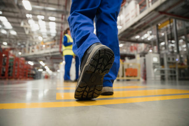 Close-Up of a Workers Boot Close-up shot of a workers boot as they walk across the factory floor. boot stock pictures, royalty-free photos & images