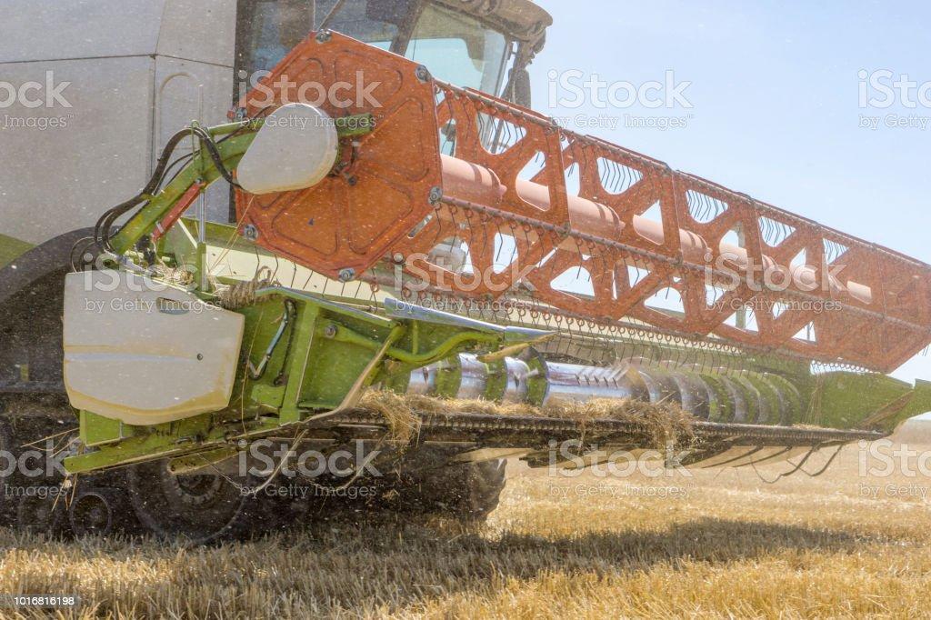 Close-up de uma colhedora de trabalho está na época da colheita. Um fertilizante de poeira e palha. Conceito de agricultura e agricultura. - foto de acervo