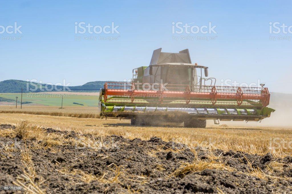 Close-up de uma colhedora de trabalho está na época da colheita. Um fertilizante de poeira e palha. Conceito de agricultura e agricultura. Copie o espaço. - foto de acervo