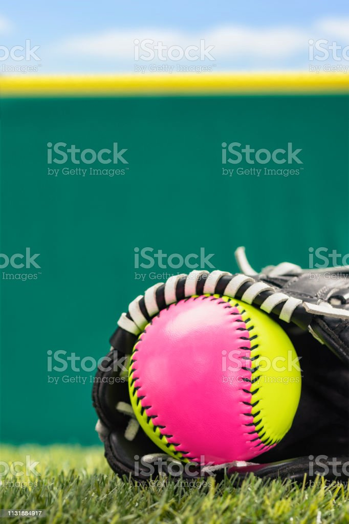 A low angle close-up view of a pink and yellow softball in the...