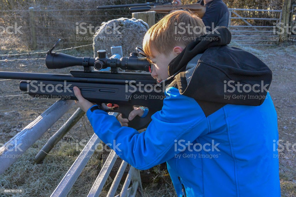 Close-up of a young boy shooting with air rifle stock photo