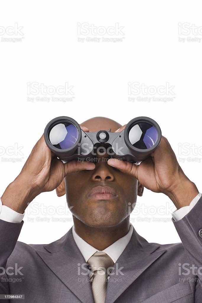 Closeup of a young businessman looking through binoculars royalty-free stock photo