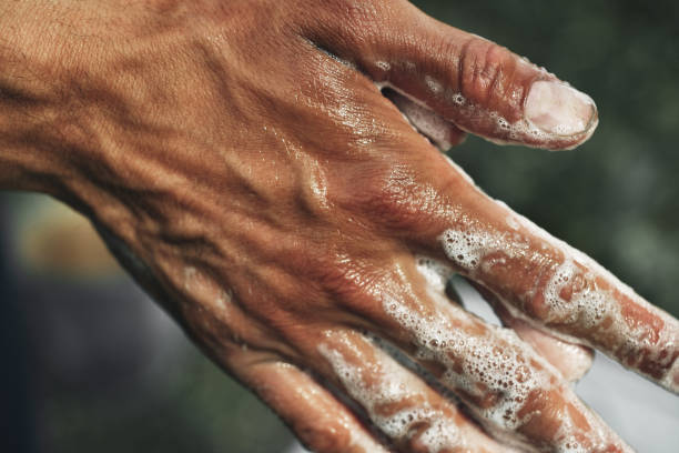 Close-up of a young Caucasian man washing his hands stock photo
