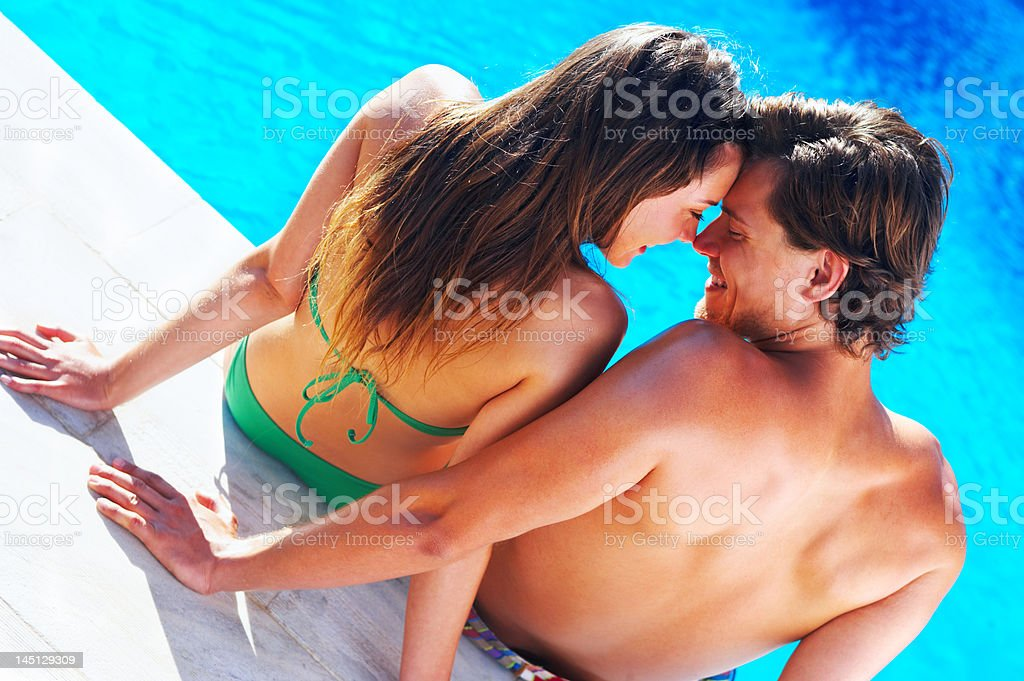 Close-up of a young couple romancing at the swimming pool royalty-free stock photo