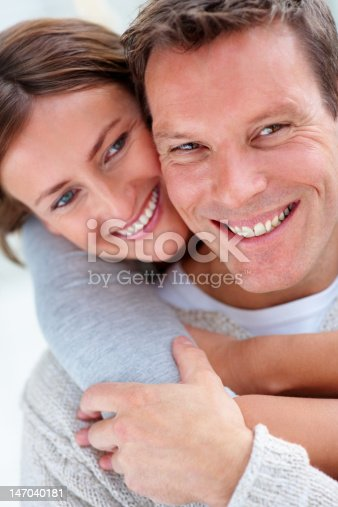 istock Close-up of a young couple smiling and embracing 147040181