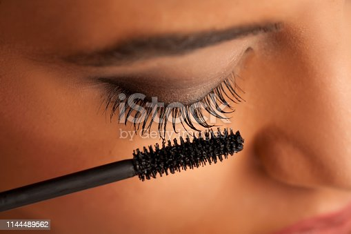 istock closeup of a young dark-skinned woman applying mascara on a white background 1144489562
