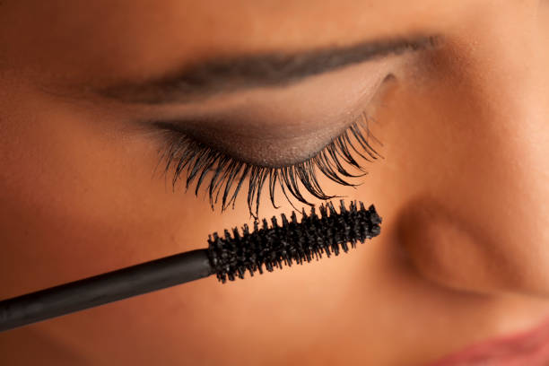 closeup of a young dark-skinned woman applying mascara on a white background stock photo