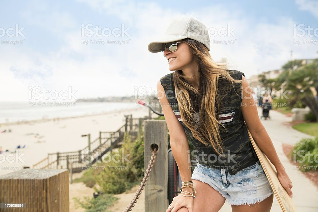 Close-up of a young girl carrying skateboard and smiling. stock photo