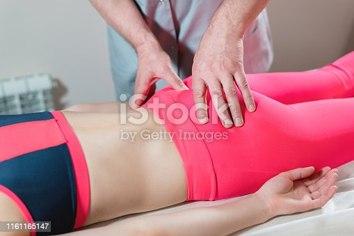 istock Close-up of a young girl's spine base editing by a male physiotherapist of visceral massage. 1161165147