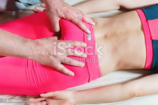 istock Close-up of a young girl's spine base editing by a male physiotherapist of visceral massage. 1161165344